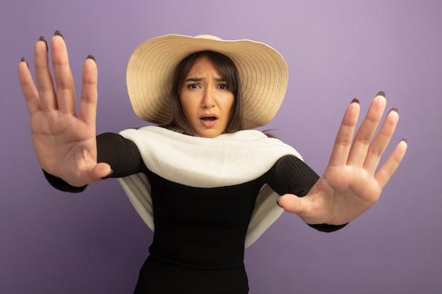 Młoda kobieta z białym szalikiem i letnim kapeluszem przestraszona trzymając się za ręce