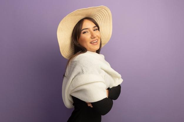 Młoda kobieta z białym szalikiem i letnim kapeluszem uśmiecha się radośnie