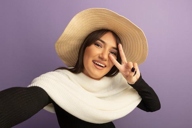 Młoda kobieta z białym szalikiem i letnim kapeluszem, uśmiechając się radośnie, pokazując znak v