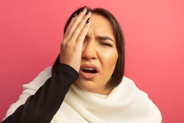 Młoda kobieta z białym szalikiem jest niezadowolona i zdezorientowana zakrywając twarz ręką