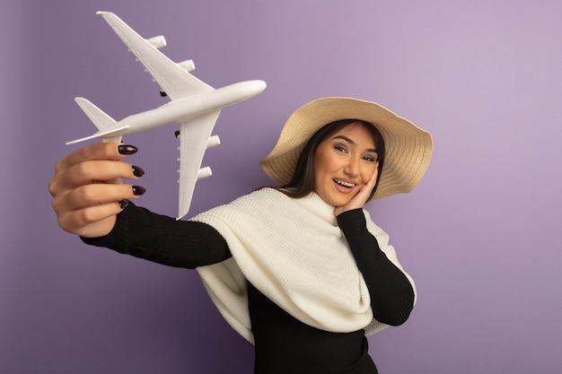 Młoda kobieta z białym szalikiem w letnim kapeluszu pokazuje samolocik szczęśliwy i wesoły uśmiechnięty
