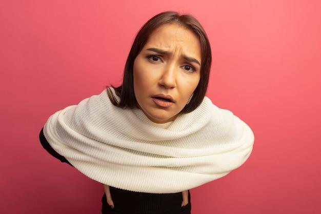 Młoda kobieta z białym szalikiem z zmieszanym wyrazem