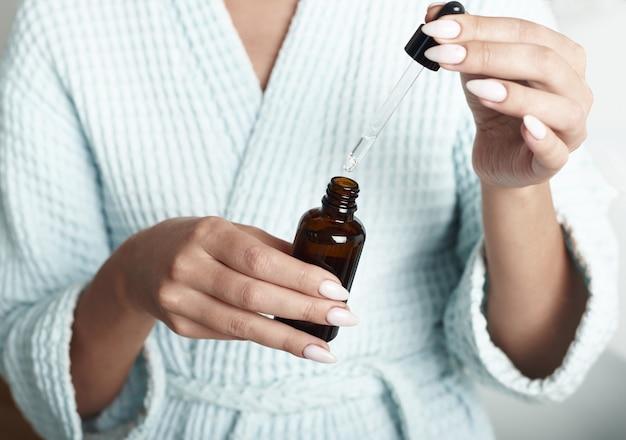 Młoda kobieta z bielactwem nabytym używa serum nawilżającego