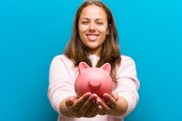 Młoda kobieta z błękitnym prosiątko bankiem