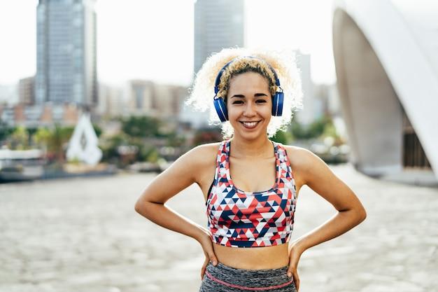 Młoda kobieta z blond kędzierzawym włosy robi sportowi plenerowemu podczas gdy słuchający muzyczną listę odtwarzania