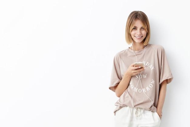 Młoda kobieta z bobped włosów na sobie ubranie, słuchanie muzyki