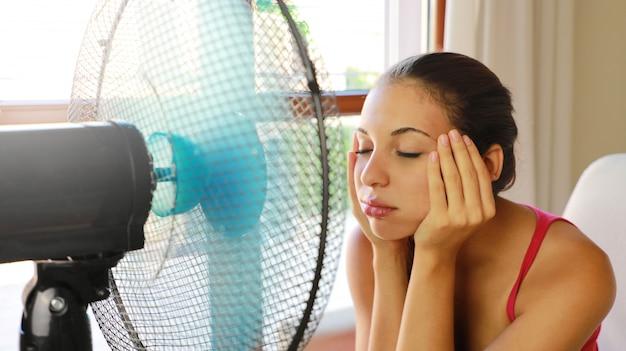 Młoda kobieta z bólem głowy cierpiąca na falę upałów i korzystająca z wentylatora siedząca na kanapie w salonie w domu.
