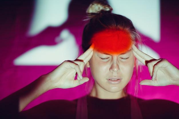 Młoda kobieta z bólem głowy i czerwonym kolorem czoła