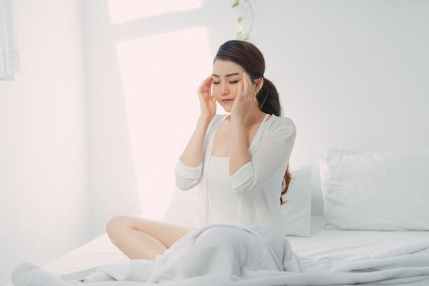 Młoda kobieta z bólem głowy siedzi na łóżku i dotyka skroni