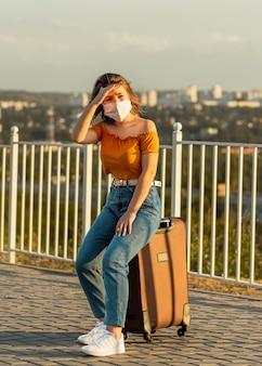 Młoda kobieta z brązowymi włosami, ubrana w maskę chirurgiczną, siedząc na walizce w parku, odwracając wzrok.