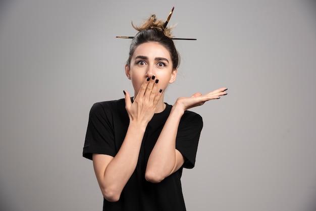 Młoda kobieta z brudną kok obejmującą usta.