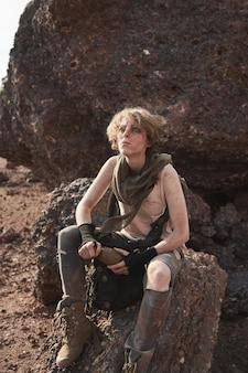 Młoda kobieta z brudną twarzą spoczywającą na kamieniu na pustyni i pijącą wodę