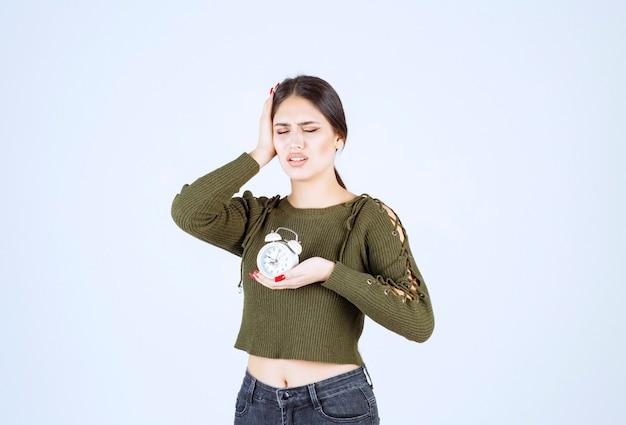 Młoda kobieta z budzikiem ma ból głowy na białym tle.