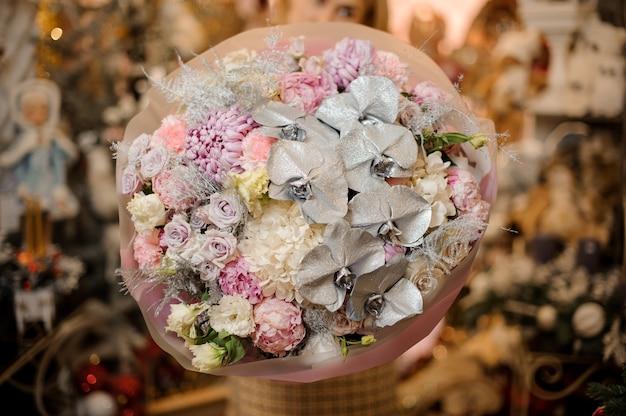 Młoda kobieta z bukietem róż, hortensji i srebrnych orchidei