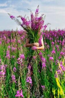 Młoda kobieta z bukietem różowych kwiatów.