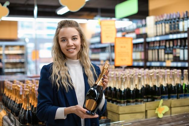 Młoda kobieta z butelką napoju alkoholowego w sklepie monopolowym. właściciel małej firmy