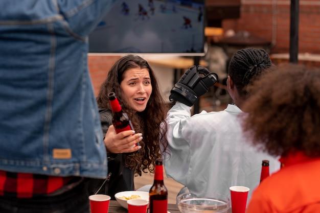 Młoda kobieta z butelką piwa rozmawia z jednym z przyjaciół podczas oglądania transmisji meczu hokejowego