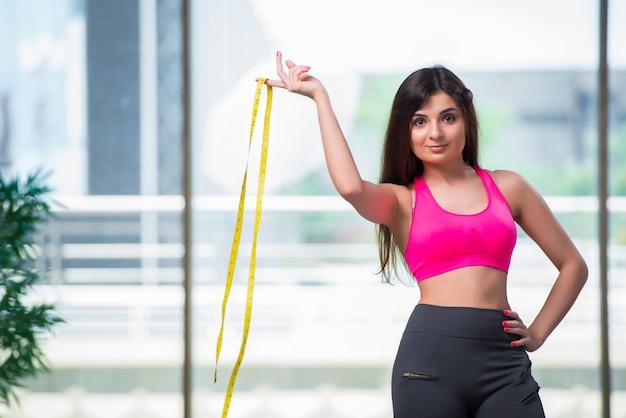 Młoda kobieta z centymetr w koncepcji utraty wagi
