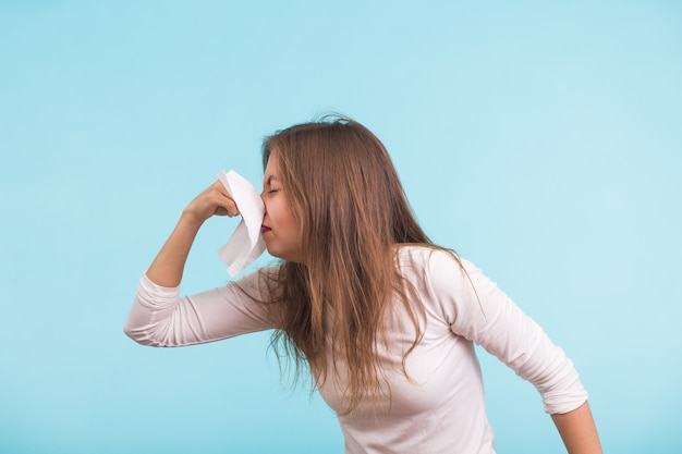 Młoda kobieta z chusteczką, ma katar na niebieskiej ścianie