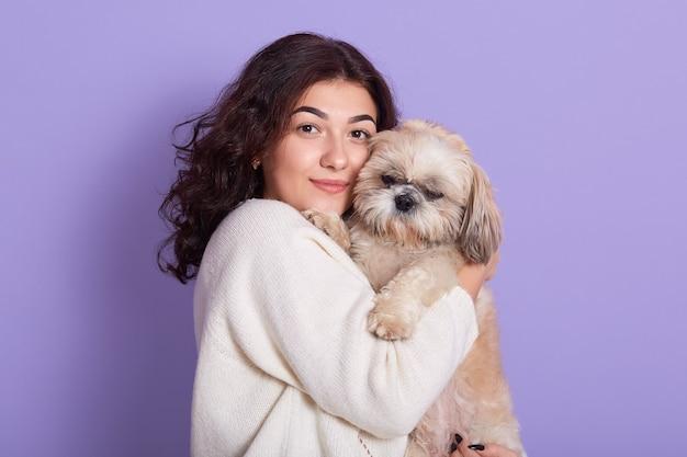 Młoda kobieta z ciemnymi falującymi włosami trzymająca w dłoniach pekińczyka, która go przytula, pani patrzy wprost, suczka ze swoim ulubionym szczeniakiem, dziewczyna ubrana w ciepły biały sweter z dzianiny na liliowej ścianie.