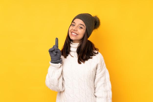 Młoda kobieta z czapka zimowa na pojedyncze żółte ściany pokazując i podnosząc palec na znak najlepszych