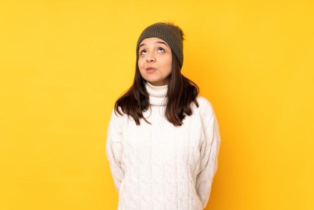 Młoda kobieta z czapka zimowa na żółty mur i patrząc w górę