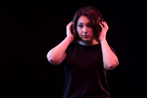 Młoda kobieta z czarną koszulką za pomocą słuchawek