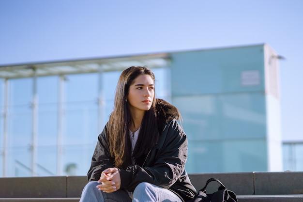 Młoda kobieta z czarną kurtką siedzi na betonowych schodach z zaciśniętymi rękami patrząc na bok