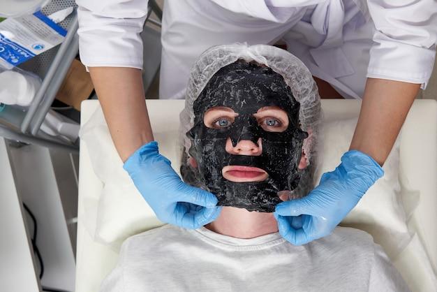 Młoda kobieta z czarną maską tlenową na twarzy w salonie kosmetycznym