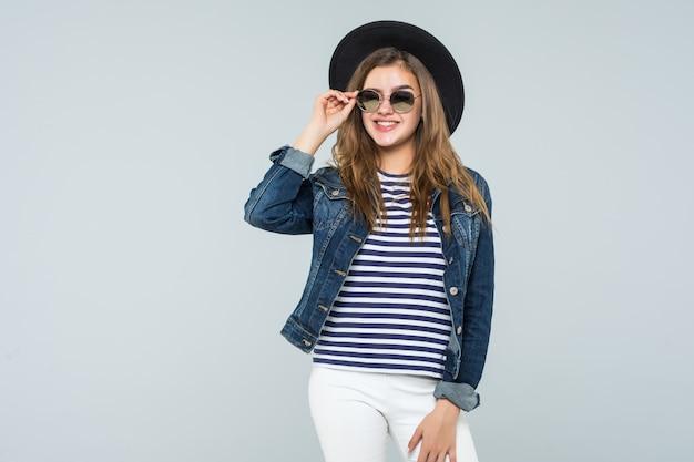 Młoda kobieta z czarnym kapeluszem i okularami przeciwsłonecznymi odizolowywającymi na białym tle
