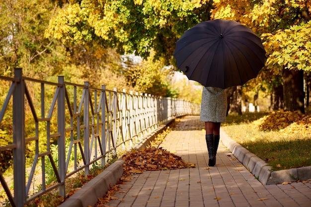 Młoda kobieta z czarnym parasolem w parku