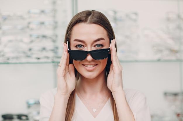 Młoda kobieta z czarnymi dziurkowanymi okularami do treningu wzroku. trener okularów perforowanych