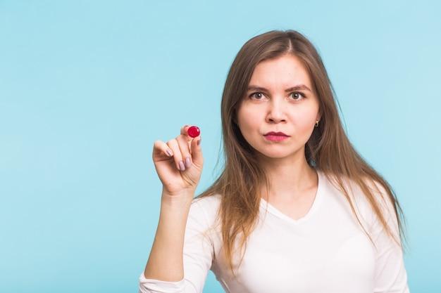 Młoda kobieta z czerwoną tabletką na niebieskim tle. pojęcie zdrowia, chorób i ludzi