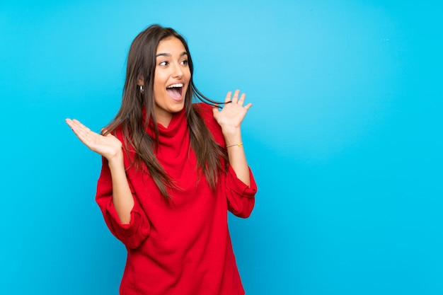 Młoda kobieta z czerwonym swetrem z niespodzianką wyraz twarzy