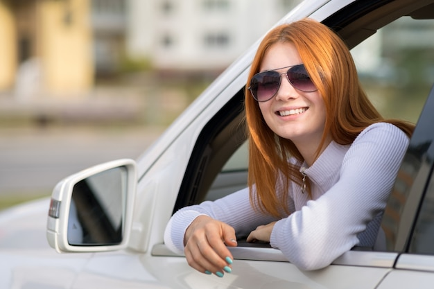 Młoda kobieta z czerwonym włosy jedzie samochód.