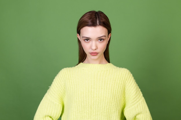 Młoda kobieta z czystą idealną naturalną skórą i makijażem brązowe duże usta na zielonej ścianie pozowanie