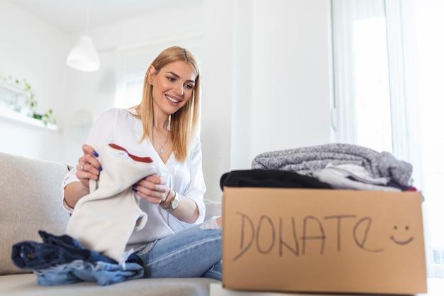 Młoda kobieta z darowizny pudełkiem w domu. pudełko na darowizny dla ubogich z odzieżą w rękach kobiet. kobieta przekazuje ubrania do schroniska. wesoła kobieta trzyma pudełko podarowanych ubrań