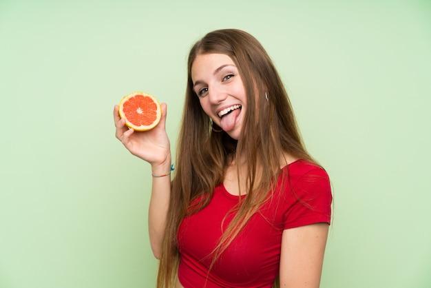 Młoda kobieta z długie włosy mieniem grapefruitowy