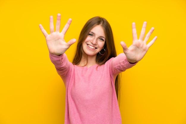Młoda kobieta z długie włosy nad odosobnioną żółtą ścianą liczy dziesięć z palcami