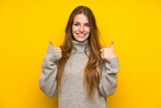 Młoda kobieta z długie włosy nad żółtym tłem daje aprobata gestowi