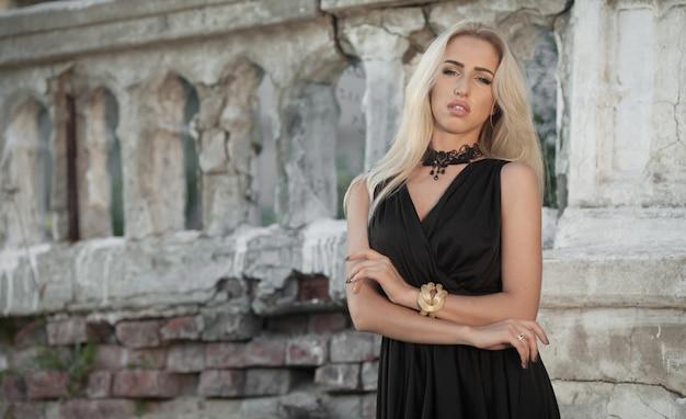 Młoda kobieta z długimi blond włosami w czarnej sukni portret na zewnątrz. delikatne, słoneczne kolory. zamknij portret. sesja mody.
