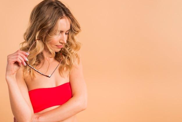 Młoda kobieta z długimi blond włosami w czerwonym top gospodarstwa okulary