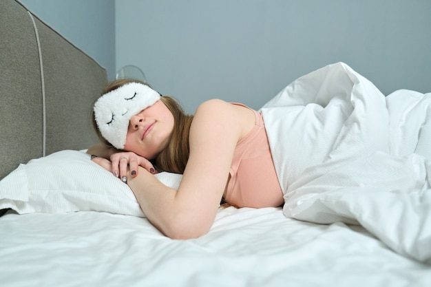Młoda kobieta z długimi blond włosami z maską do spania w oczach śpi w białym łóżku