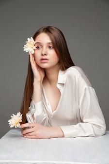 Młoda kobieta z długimi brązowymi włosami zakrywającymi oko naturalnym kwiatem i odwracająca wzrok siedząc przy stole na szarym tle