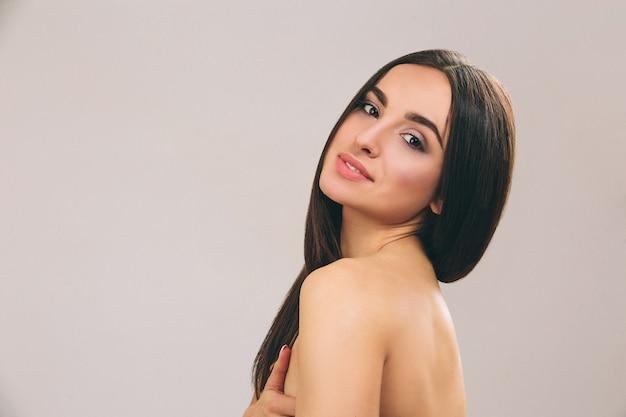 Młoda kobieta z długimi czarnymi włosami pozowanie. brunetka wygląda prosto i uśmiecha się. nagie ciało