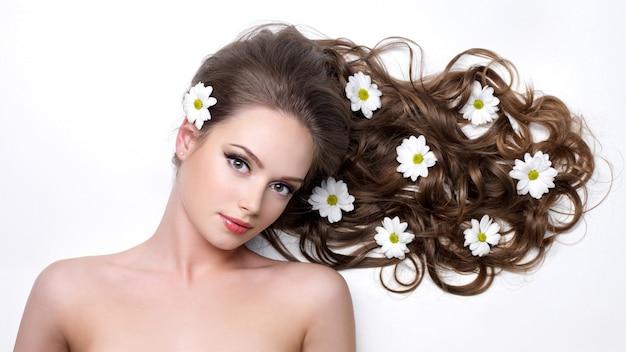Młoda kobieta z długimi kręconymi włosami i rumiankami w nim na białym tle