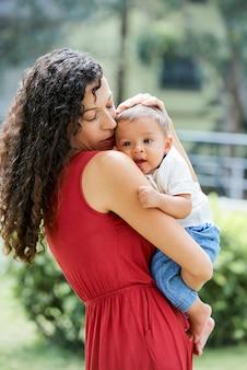 Młoda kobieta z długimi kręconymi włosami, trzymająca swojego małego synka i delikatnie głaszcząca jego głowę