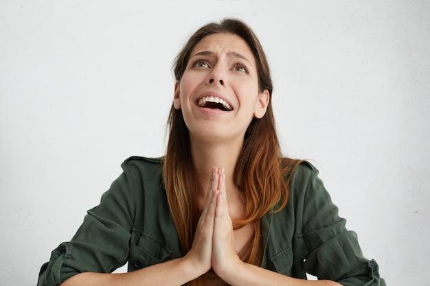 Młoda kobieta z długimi prostymi włosami błagająca o coś, co trzyma dłonie razem, patrząc smutno na izolację.