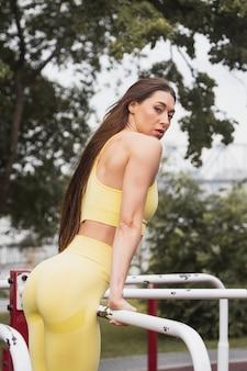 Młoda kobieta z długimi prostymi włosami na treningu ulicy podciąga się na nierównych prętach na boisku sportowym w parku, widok z tyłu