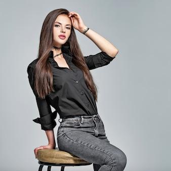 Młoda kobieta z długimi prostymi włosami - w studio. portret atrakcyjna brunetka dziewczyna. modelka nosi czarną koszulę i dżinsy. seksowna modelka